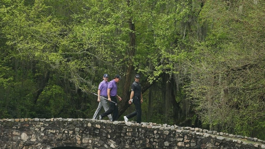 From left, Brandt Snedeker, Phil Mickelson and Dustin Johnson walk across the Nelson Bridge during a practice round for the Masters golf tournament Tuesday, April 7, 2015, in Augusta, Ga. (AP Photo/Charlie Riedel)