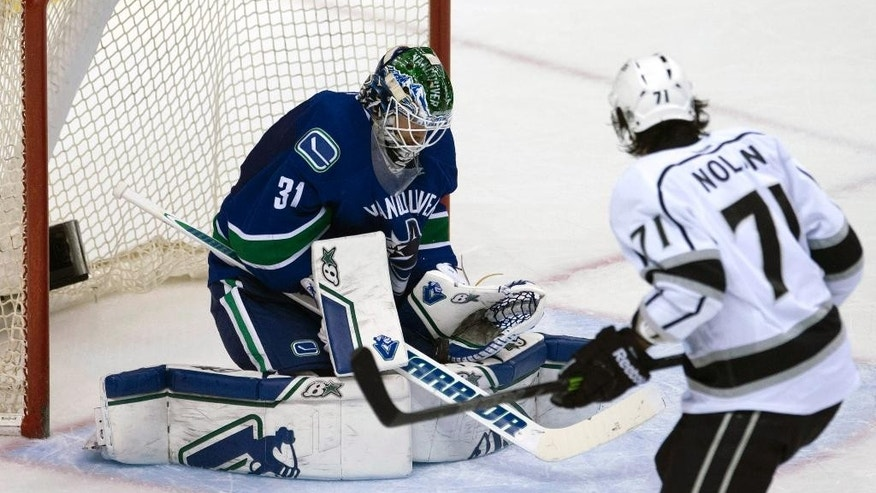 Vancouver Canucks goalie Eddie Lack (31) stops a shot from Los Angeles Kings center Jordan Nolan (71) during the second period of an NHL hockey game in Vancouver, British Columbia, Monday, April 6, 2015. (AP Photo/The Canadian Press, Jonathan Hayward)