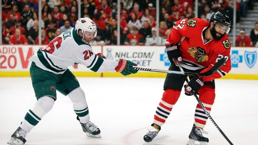 Chicago Blackhawks defenseman Johnny Oduya (27) looks to pass the puck against Minnesota Wild left wing Thomas Vanek (26) during the first period of an NHL hockey game Tuesday, April 7, 2015, in Chicago. (AP Photo/Kamil Krzaczynski)