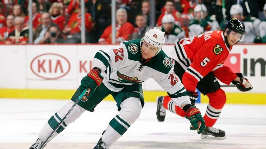 Minnesota Wild right wing Nino Niederreiter (22) controls the puck against Chicago Blackhawks defenseman David Rundblad (5) during the first period of an NHL hockey game Tuesday, April 7, 2015, in Chicago. (AP Photo/Kamil Krzaczynski)