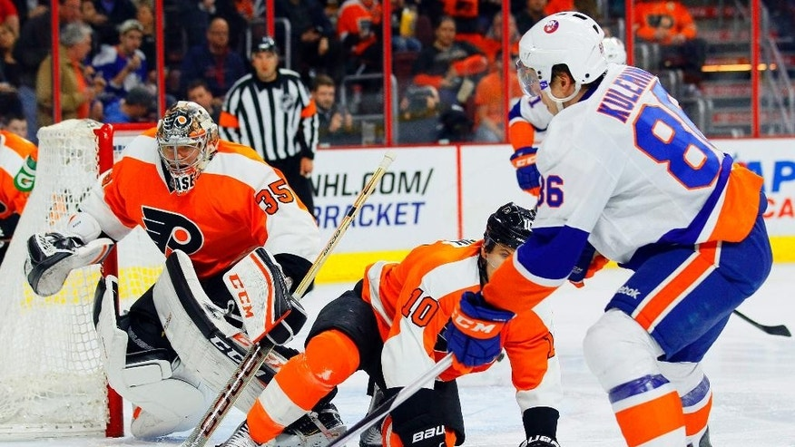 New York Islanders' Nikolay Kulemin, right, moves to get the rebounding puck as Philadelphia Flyers goalie Steve Mason, left, and Brayden Schenn, center, defend during the first period of an NHL hockey game, Tuesday, April 7, 2015, in Philadelphia. (AP Photo/Tom Mihalek)