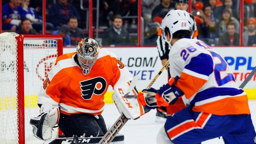 New York Islanders' Tyler Kennedy, right, takes a shot on goal stopped by Philadelphia Flyers' Steve Mason in the first period of an NHL hockey game, Tuesday, April 7, 2015, in Philadelphia. (AP Photo/Tom Mihalek)
