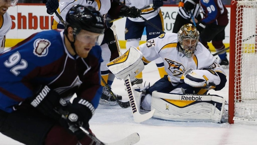 Nashville Predators goalie Pekka Rinne (35), of Finland, watches as Colorado Avalanche left wing Gabriel Landeskog (92), of Sweden, head for the puck during the first period of an NHL hockey game Tuesday, April 7, 2015, in Denver. (AP Photo/David Zalubowski)