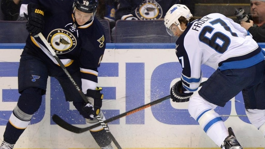 St. Louis Blues' Jay Bouwmeester (19) and Winnipeg Jets' Michael Frolik (67), of the Czech Republic, battle for the puck during the first period of an NHL hockey game, Tuesday, April 7, 2015, in St. Louis. (AP Photo/Bill Boyce)