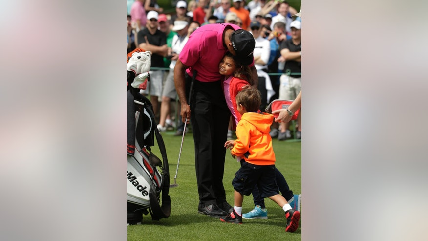 Tiger Woods greets his children Charlie, left and Sam during a practice round for the Masters golf tournament Tuesday, April 7, 2015, in Augusta, Ga. (AP Photo/Chris Carlson)