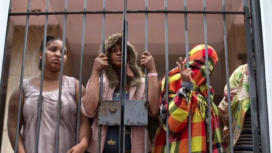 People stand behind a gate at the entrance of an abandoned residential apartment building in the middle class Flamengo neighborhood of Rio de Janeiro, Brazil, Tuesday, April 7, 2015. Squatters invaded the residence that Brazil's one-time richest man was supposed to transform into a luxury hotel, ahead of the 2016 Olympic games and are demanding city officials put them into social housing. (AP Photo/Silvia Izquierdo)