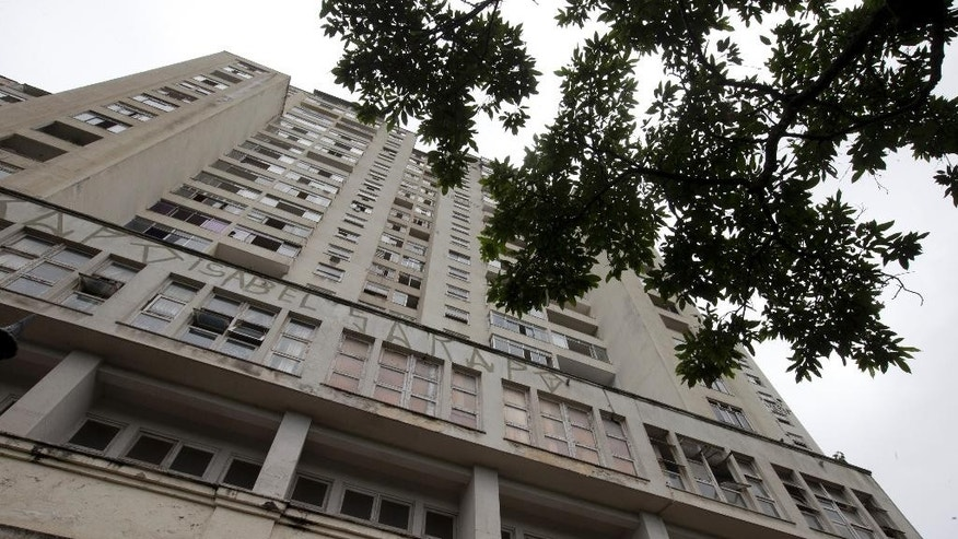 An abandoned building stands in the middle class Flamengo neighborhood of Rio de Janeiro, Brazil, Tuesday, April 7, 2015. Over the past two evenings, squatters invaded this residence that Brazil's one-time richest man, Eike Batista, was supposed to transform into a luxury hotel ahead of the 2016 Olympic games. The squatters are demanding city officials put them into social housing. (AP Photo/Silvia Izquierdo)