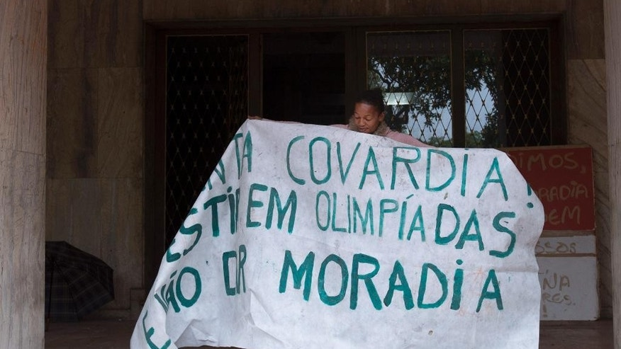 """A woman holds open a banner that reads in Portuguese """"Such cowardice. Investment in Olympics and not housing"""" to show it to the press and neighbors from inside an abandoned building in the middle class Flamengo neighborhood of Rio de Janeiro, Brazil, Tuesday, April 7, 2015. Over the past two evenings, squatters invaded this residence that Brazil's one-time richest man, Eike Batista, was supposed to transform into a luxury hotel ahead of the 2016 Olympic games. The squatters are demanding city officials put them into social housing. (AP Photo/Silvia Izquierdo)"""