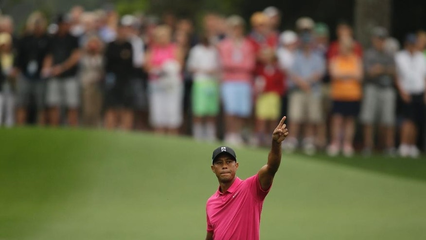Tiger Woods points to his shot on the eighth fairway during a practice round for the Masters golf tournament Tuesday, April 7, 2015, in Augusta, Ga. (AP Photo/Matt Slocum)