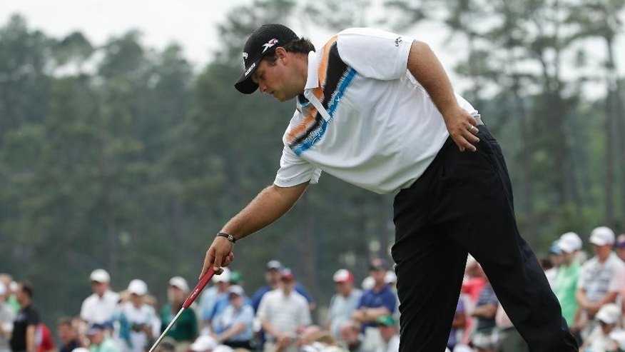 Patrick Reed reaches for a ball on the 18th green during a practice round for the Masters golf tournament Tuesday, April 7, 2015, in Augusta, Ga. (AP Photo/Charlie Riedel)