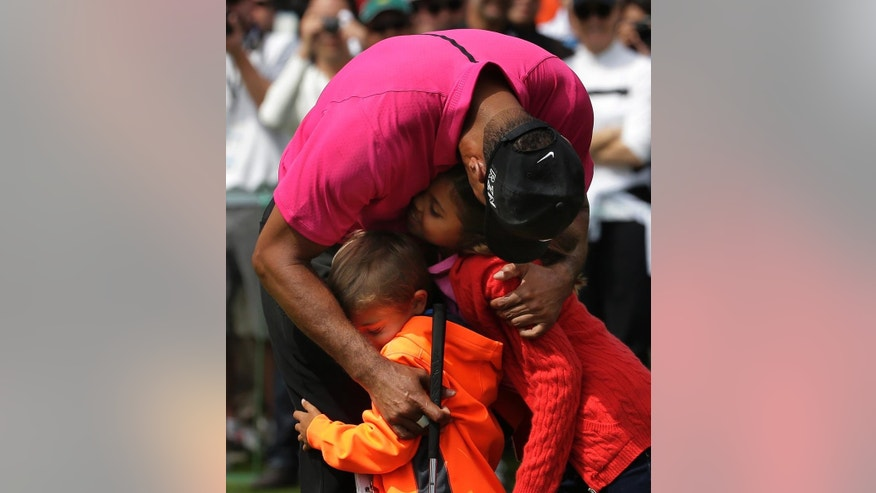 Tiger Woods hugs his children Charlie, left and Sam during a practice round for the Masters golf tournament Tuesday, April 7, 2015, in Augusta, Ga. (AP Photo/Chris Carlson)