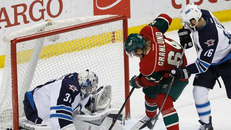 Winnipeg Jets goalie Ondrej Pavelec (31), of the Czech Republic, deflects a shot by Minnesota Wild center Mikael Granlund (64), of Finland, as Jets left wing Andrew Ladd, right, defends, during the first period of an NHL hockey game in St. Paul, Minn., Monday, April 6, 2015. (AP Photo/Ann Heisenfelt)