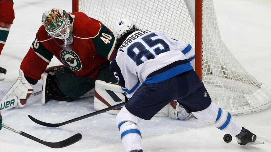 Minnesota Wild goalie Devan Dubnyk (40) deflects a shot under Winnipeg Jets center Mathieu Perreault (85) during the first period of an NHL hockey game in St. Paul, Minn., Monday, April 6, 2015. (AP Photo/Ann Heisenfelt)