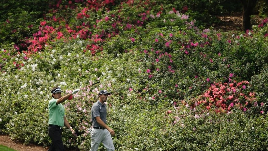 Bubba Watson walks down the 12th fairway with Geoff Ogilvy, of Australia, during a practice round for the Masters golf tournament Tuesday, April 7, 2015, in Augusta, Ga. (AP Photo/Matt Slocum)