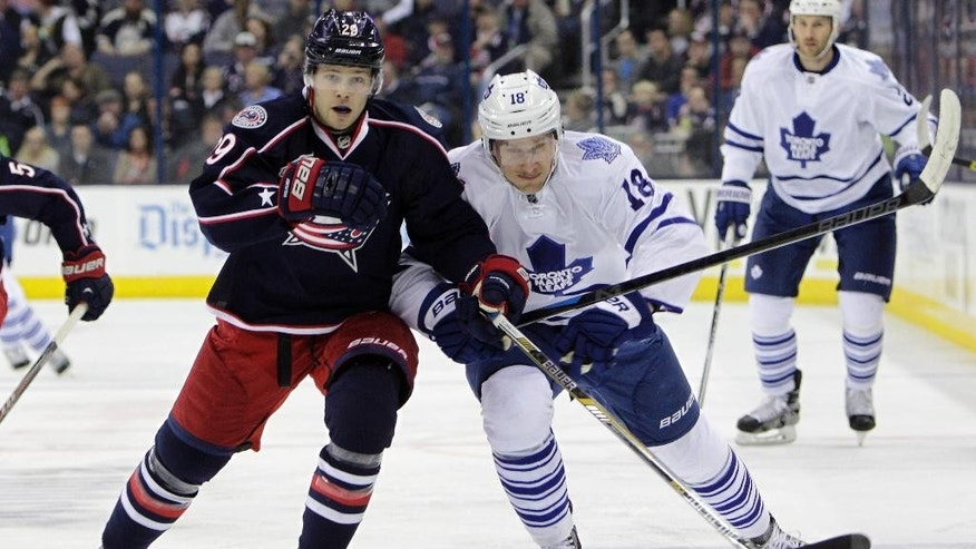 Columbus Blue Jackets' Cody Goloubef, left, and Toronto Maple Leafs' Richard Panik chase a loose puck during the first period of an NHL hockey game Wednesday, April 8, 2015, in Columbus, Ohio. (AP Photo/Jay LaPrete)