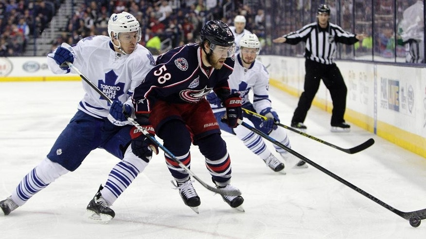 Toronto Maple Leafs'  David Booth, left, and Columbus Blue Jackets' David Savard chase a loose puck during the first period of an NHL hockey game Wednesday, April 8, 2015, in Columbus, Ohio. (AP Photo/Jay LaPrete)