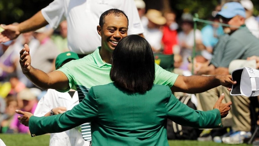 Tiger Woods hugs former Secretary of State Condoleeza Rice during the Par 3 contest at the Masters golf tournament Wednesday, April 8, 2015, in Augusta, Ga. Behind is Lindsey Vonn and Tiger's children Sam and Charlie. (AP Photo/Matt Slocum)
