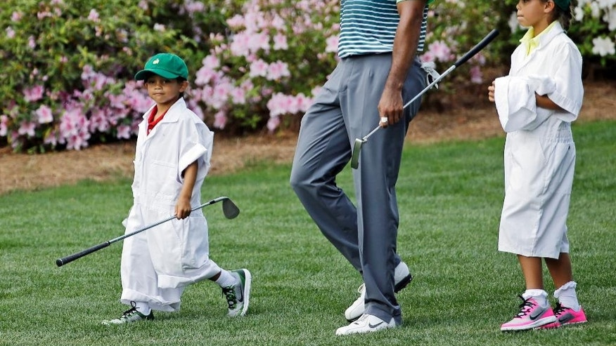 Tiger Woods walks with his children Sam and Charlie during the Par 3 contest at the Masters golf tournament Wednesday, April 8, 2015, in Augusta, Ga. (AP Photo/David J. Phillip)