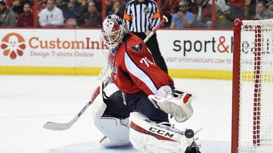 Washington Capitals goalie Braden Holtby reaches for the puck during the second period of an NHL hockey game against the Boston Bruins, Wednesday, April 8, 2015, in Washington. (AP Photo/Nick Wass)