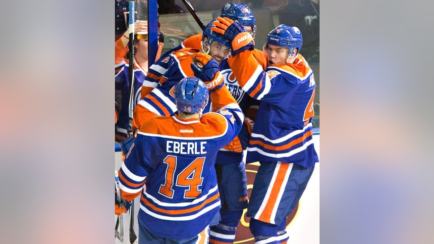 Edmonton Oilers' Jordan Eberle (14), Benoit Pouliot (67), Matt Fraser (28) and Taylor Hall (4) celebrate a goal against the Los Angeles Kings during the second period of an NHL hockey game Tuesday, April 7, 2015, in Edmonton, Alberta. (AP Photo/The Canadian Press, Jason Franson)