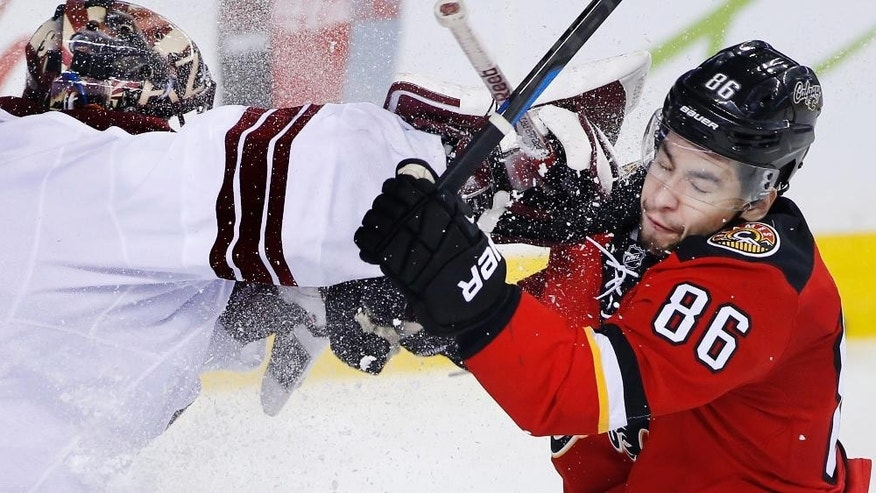 Arizona Coyotes goalie Mike Smith, left, tangles with Calgary Flames' Josh Jooris uring the third period of an NHL hockey game Tuesday, April 7, 2015, in Calgary, Alberta. (AP Photo/The Canadian Press, Larry MacDougal)