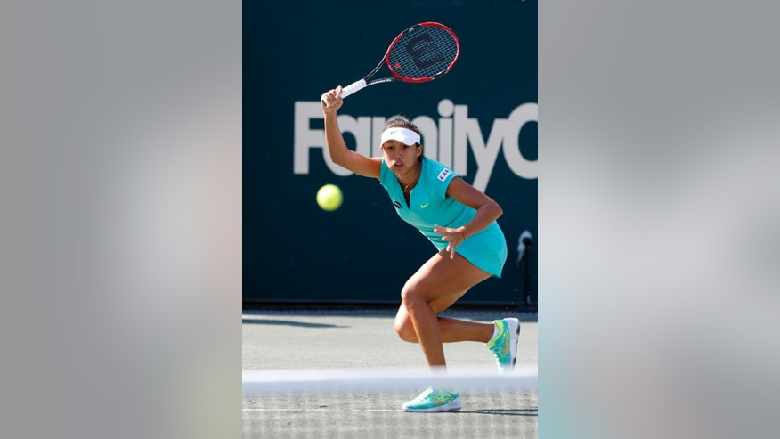 Shuai Zhang, of China, returns to Ekaterina Makarova during a match at the Family Circle Cup tennis tournament in Charleston, S.C., Wednesday, April 8, 2015. (AP Photo/Mic Smith)