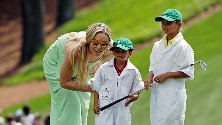 Lindsey Vonn and Tiger Woods' children Sam and Charlie watch Tiger during the Par 3 contest at the Masters golf tournament Wednesday, April 8, 2015, in Augusta, Ga. (AP Photo/Charlie Riedel)