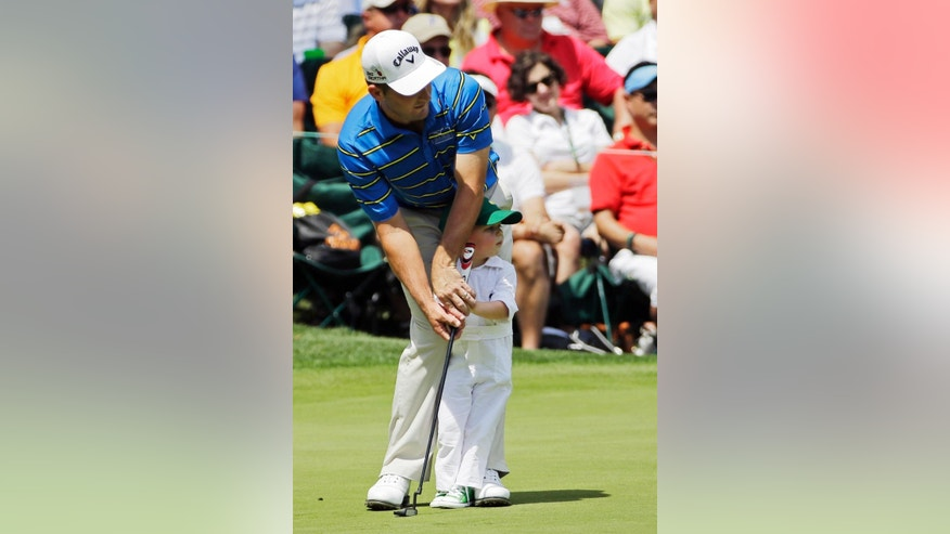 Matt Every helps his son Liam during the Par 3 contest at the Masters golf tournament Wednesday, April 8, 2015, in Augusta, Ga. (AP Photo/David J. Phillip)