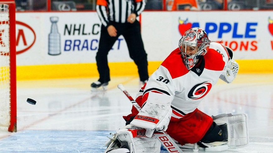 Carolina Hurricanes' Cam Ward watches the puck go wide of the net after a face-off in the second period of an NHL hockey game against the Philadelphia Flyers, Thursday, April 9, 2015, in Philadelphia.(AP Photo/Tom Mihalek)