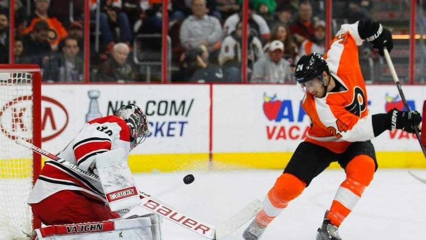 Carolina Hurricanes goalie Cam Ward, left, defends on a shot while Philadelphia Flyers' Matt Read watches during the second period of an NHL hockey game, Thursday, April 9, 2015, in Philadelphia.(AP Photo/Tom Mihalek)