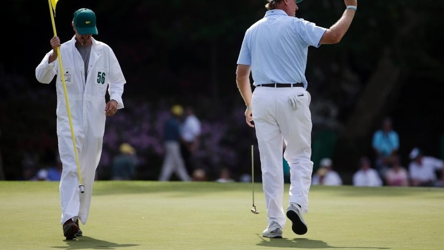 Ernie Els, of South Africa, holds up his ball after putting on the 15th green during the first round of the Masters golf tournament Thursday, April 9, 2015, in Augusta, Ga. (AP Photo/Darron Cummings)