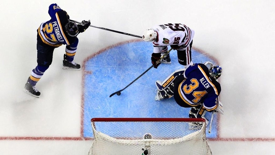 Chicago Blackhawks' Andrew Shaw scores past St. Louis Blues goalie Jake Allen (34) as Blues' Alex Pietrangelo, left, defends during the third period of an NHL hockey game Thursday, April 9, 2015, in St. Louis. The Blues won 2-1. (AP Photo/Jeff Roberson)