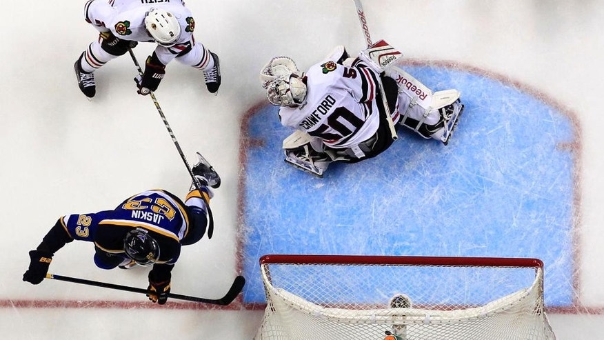 St. Louis Blues' Dmitrij Jaskin (23), of Russia, scores past Chicago Blackhawks goalie Corey Crawford (50) and Duncan Keith (2) during the second period of an NHL hockey game Thursday, April 9, 2015, in St. Louis. (AP Photo/Jeff Roberson)