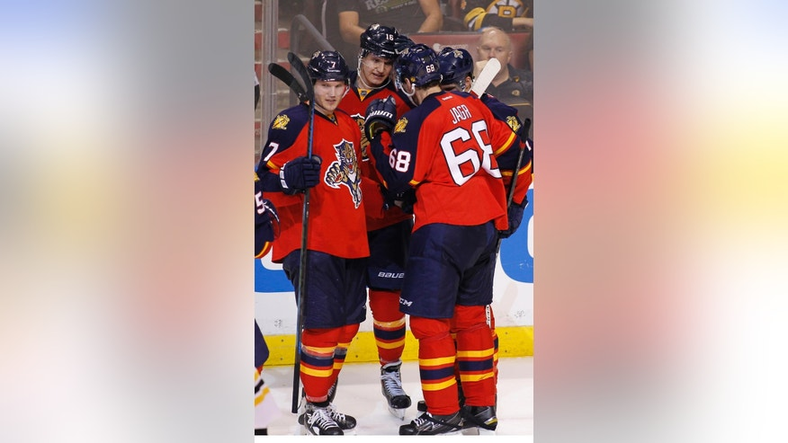 Florida Panthers center Aleksander Barkov, center, celebrates his goal with  Dmitry Kulikov (7) and Jaromir Jagr (68) during the second period of an NHL hockey game against the Boston Bruins Thursday, April 9, 2015, in Sunrise, Fla. (AP Photo/Terry Renna)