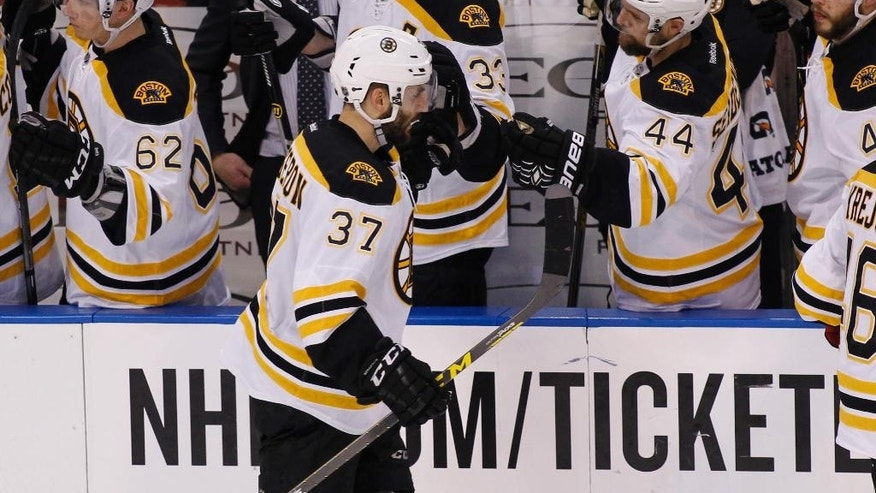 Boston Bruins center Patrice Bergeron (37) celebrates with teammates after scoring a goal during the second period of an NHL hockey game against the Florida Panthers Thursday, April 9, 2015, in Sunrise, Fla. (AP Photo/Terry Renna)