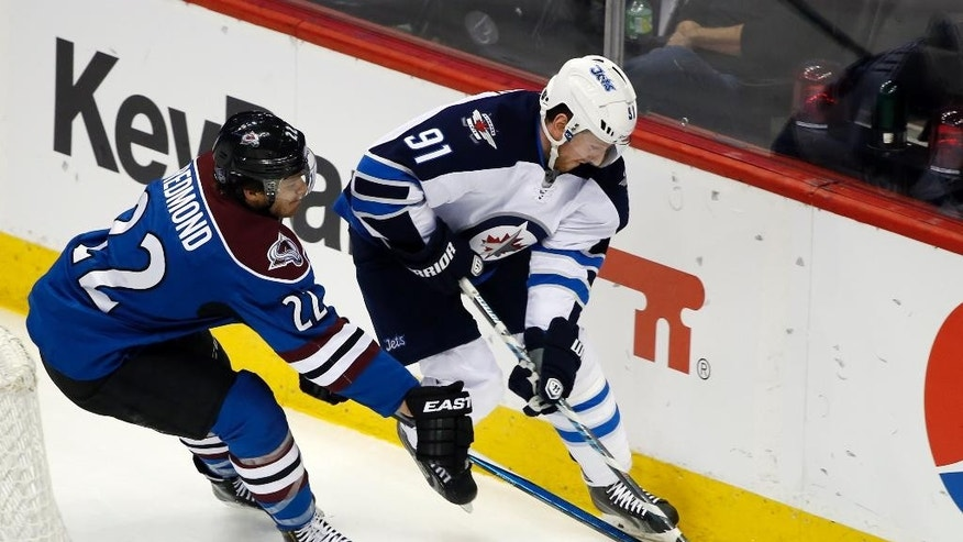 Colorado Avalanche defenseman Zach Redmond (22) steals the puck from Winnipeg Jets left wing Jiri Tlusty (91) during the first period of an NHL hockey game, Thursday, April 9, 2015, in Denver. (AP Photo/Jack Dempsey)