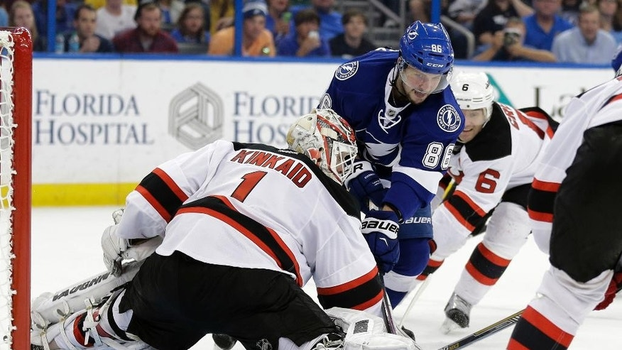 Tampa Bay Lightning right wing Nikita Kucherov (86), of Russia, misses the net after shooting against New Jersey Devils goalie Keith Kinkaid (1) during the second period of an NHL hockey game Thursday, April 9, 2015, in Tampa, Fla. Defending for the Devils is Andy Greene (6). (AP Photo/Chris O'Meara)