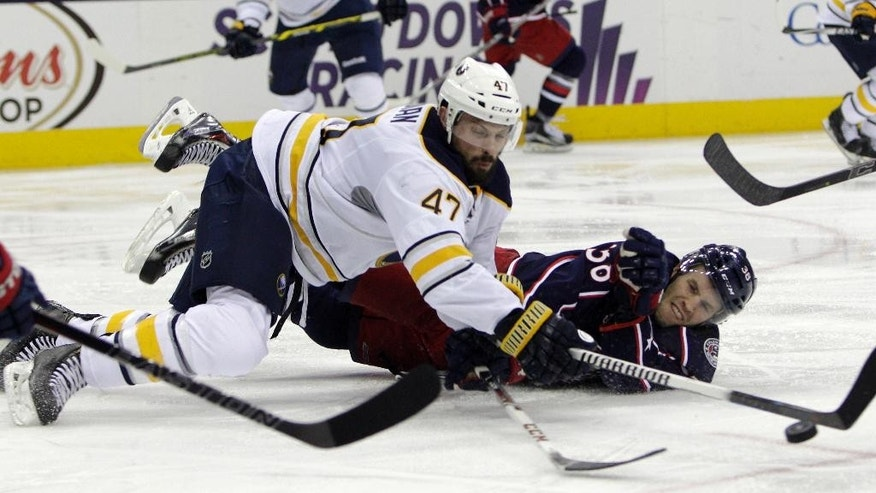 Buffalo Sabres' Zach Bogosian, left, and Columbus Blue Jackets' Boone Jenner dive for the puck during the second period of an NHL hockey game Friday, April 10, 2015, in Columbus, Ohio. (AP Photo/Jay LaPrete)