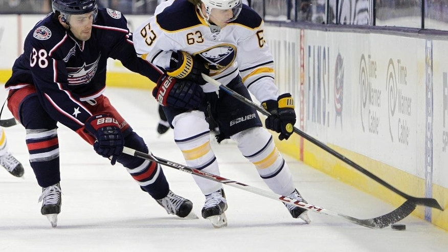 Columbus Blue Jackets' Boone Jenner, left, and Buffalo Sabres' Tyler Ennis chase the puck during the first period of an NHL hockey game Friday, April 10, 2015, in Columbus, Ohio. (AP Photo/Jay LaPrete)