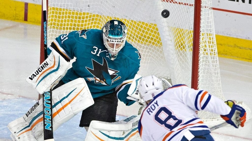 San Jose Sharks goalie Antti Niemi (31) tries to make the save as Edmonton Oilers Derek Roy (8) misses the net with his shot during the second period of an NHL hockey game, Thursday, April 9, 2015 in Edmonton, Alberta.  (AP Photo/The Canadian Press, Jason Franson)