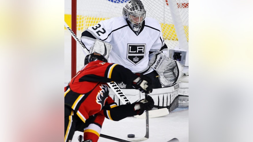 Calgary Flames' Johnny Gaudreau, left, fires a shot on Los Angeles Kings goalie Jonathan Quick during the second period of an NHL hockey game Thursday, April 9, 2015, in Calgary, Alberta. (AP Photo/The Canadian Press, Larry MacDougal)