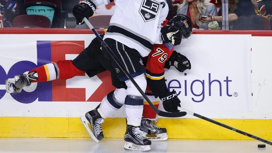 Calgary Flames' Michael Ferland, bottom, is hit into the boards by Los Angeles Kings' Anze Kopitar, from Slovenia, during the second period of an NHL hockey game Thursday, April 9, 2015, in Calgary, Alberta. (AP Photo/The Canadian Press, Larry MacDougal)