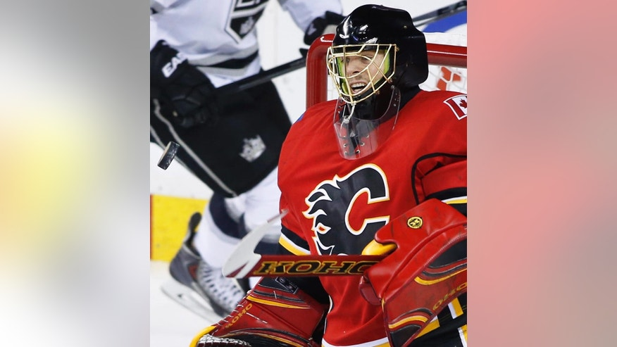 Calgary Flames goalie Jonas Hiller, from Switzerland, makes a save against the Los Angeles Kings during the first period of an NHL hockey game Thursday, April 9, 2015, in Calgary, Alberta. (AP Photo/The Canadian Press, Larry MacDougal)
