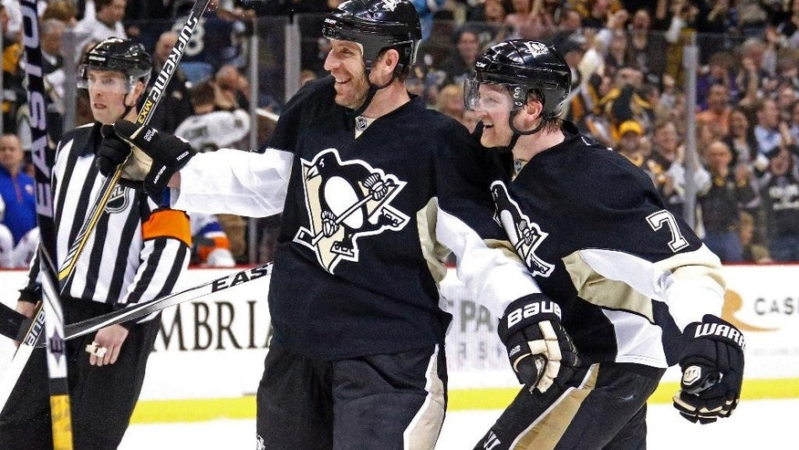 Pittsburgh Penguins' Rob Scuderi (4) celebrates his goal with teammate Paul Martin, right, during the second period of an NHL hockey game against the New York Islanders in Pittsburgh, Friday, April 10, 2015. (AP Photo/Gene J. Puskar)