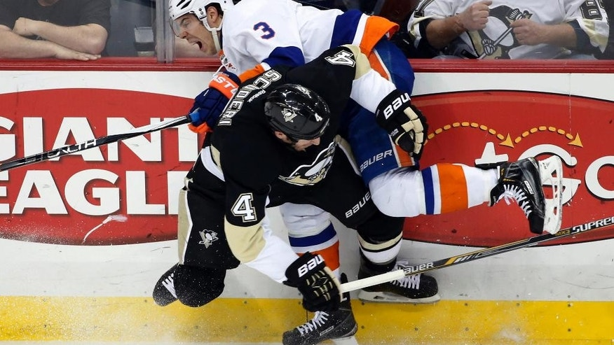 Pittsburgh Penguins' Rob Scuderi (4) collides with New York Islanders' Travis Hamonic (3) during the first period of an NHL hockey game in Pittsburgh, Friday, April 10, 2015. (AP Photo/Gene J. Puskar)