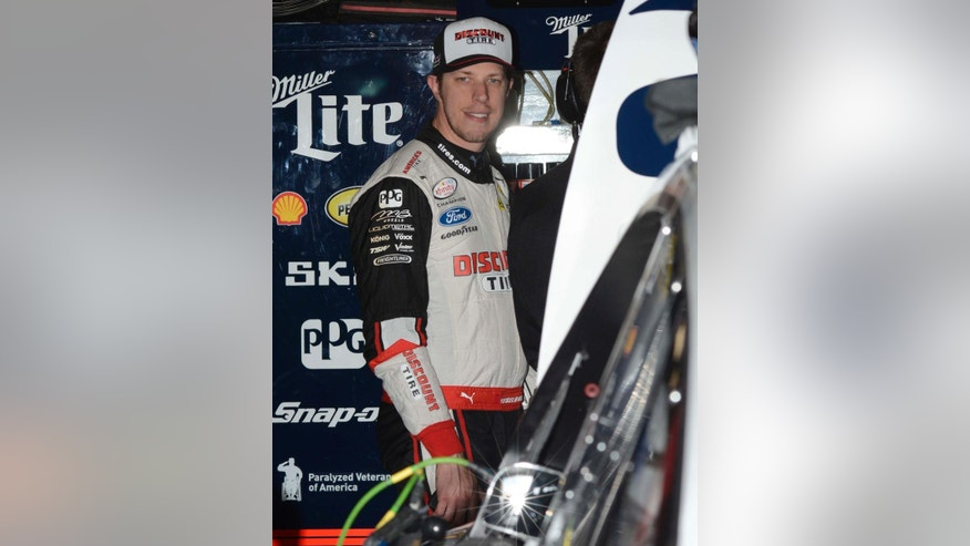 NASCAR driver Brad Keselowski (2) smiles while standing in the garage during a practice session for the Sprint Cup auto race at Texas Motor Speedway in Fort Worth, Texas, Friday, April 10, 2015. The Duck Commander 500 will run on Saturday evening. (AP Photo/Larry Papke)