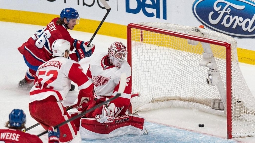 Montreal Canadiens' Jeff Petry scores past Detroit Red Wings goalie Jimmy Howard as defenseman Jonathan Ericsson looks on during the second period of an NHL hockey game, Thursday, April 9, 2015 in Montreal.  (AP Photo/The Canadian Press, Paul Chiasson)