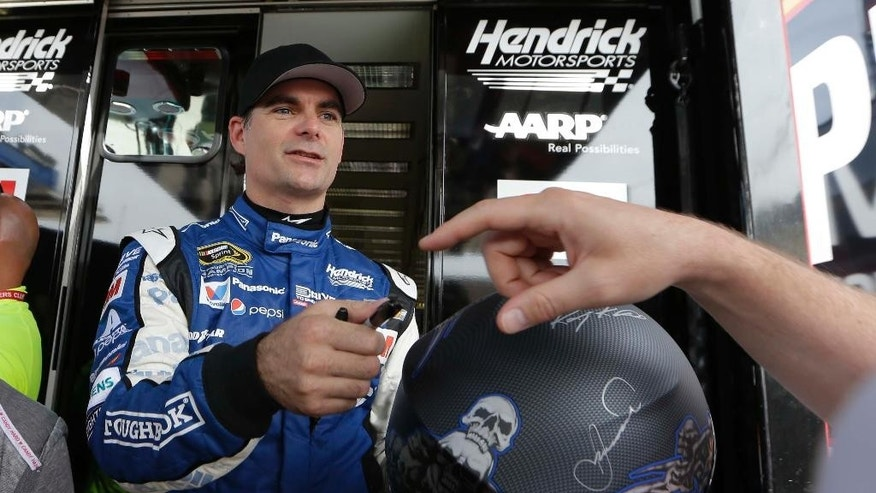 NASCAR driver Jeff Gordon signs autographs after a practice for the Sprint Cup Series auto race at Texas Motor Speedway in Fort Worth, Texas, Friday, April 10, 2015. The Duck Commander 500 will run on Saturday evening. (AP Photo/Tim Sharp)