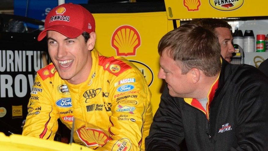 NASCAR driver Joey Logano, left, laughs while chatting with his crew in the garage during a practice session for the Sprint Cup auto race at Texas Motor Speedway in Fort Worth, Texas, Friday, April 10, 2015.  The Duck Commander 500 will run on Saturday evening. (AP Photo/Larry Papke)