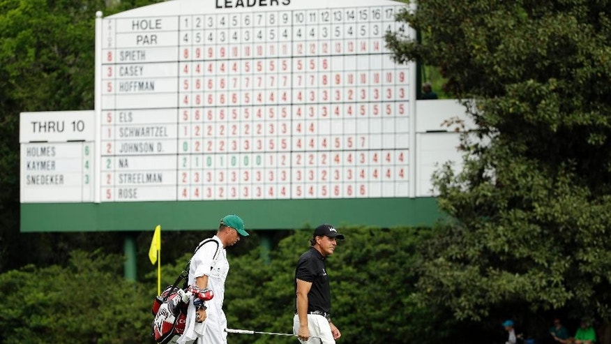 Phil Mickelson walks past a leader board on the 12th fairway during the second round of the Masters golf tournament Friday, April 10, 2015, in Augusta, Ga. (AP Photo/David J. Phillip)
